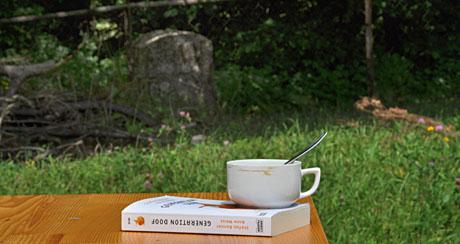 Lektüre mit Kaffee im Garten, wenige Meter von der Landesgrenze mit Berner Bär auf dem Grenzstein