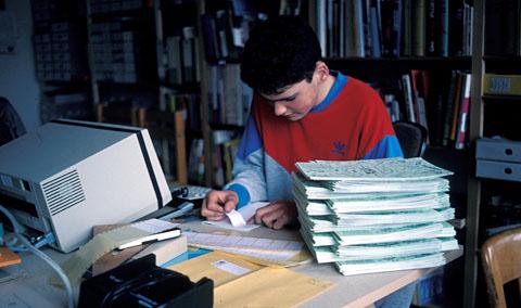 Tanner klebt Etiketten auf die fertig gehefteten FGOI-Exemplare